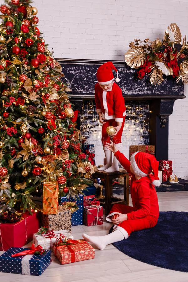 Little kids decorate the big Christmas tree. Kids and Christmas day stock image