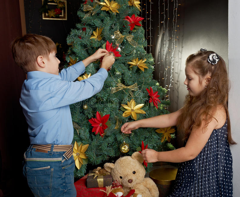 Little kids decorate Christmas. Happy little kids decorate Christmas tree in beautiful living room with traditional fire place stock photos