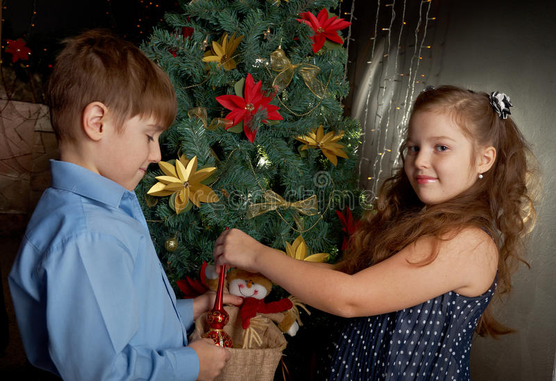 Little kids decorate Christmas. Happy little kids decorate Christmas tree in beautiful living room with traditional fire place royalty free stock images