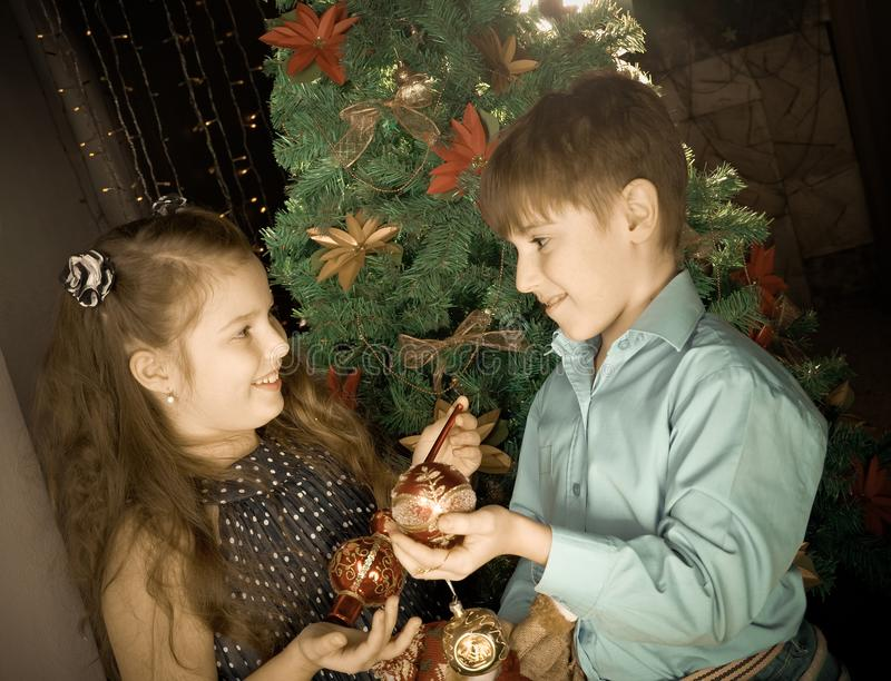 Little kids decorate Christmas tree. Happy little kids decorate Christmas tree in beautiful living room with traditional fire place stock photo