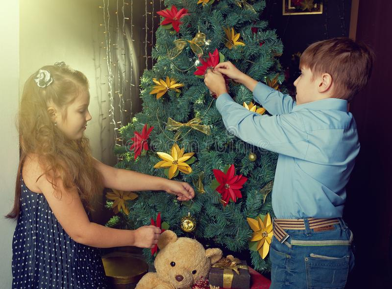 Little kids decorate Christmas tree. Happy little kids decorate Christmas tree in beautiful living room with traditional fire place royalty free stock photography