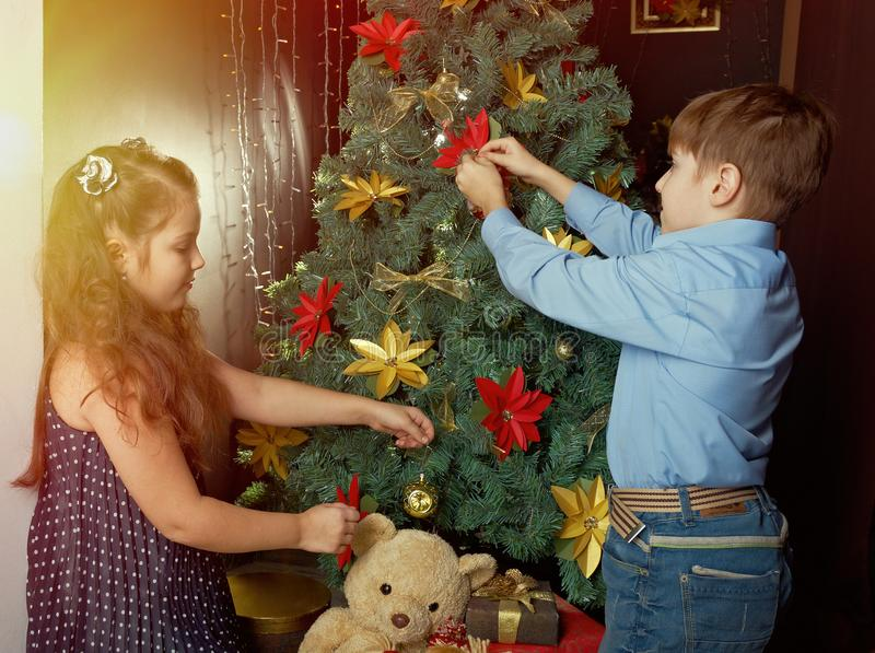 Little kids decorate Christmas tree. Happy little kids decorate Christmas tree in beautiful living room with traditional fire place stock image