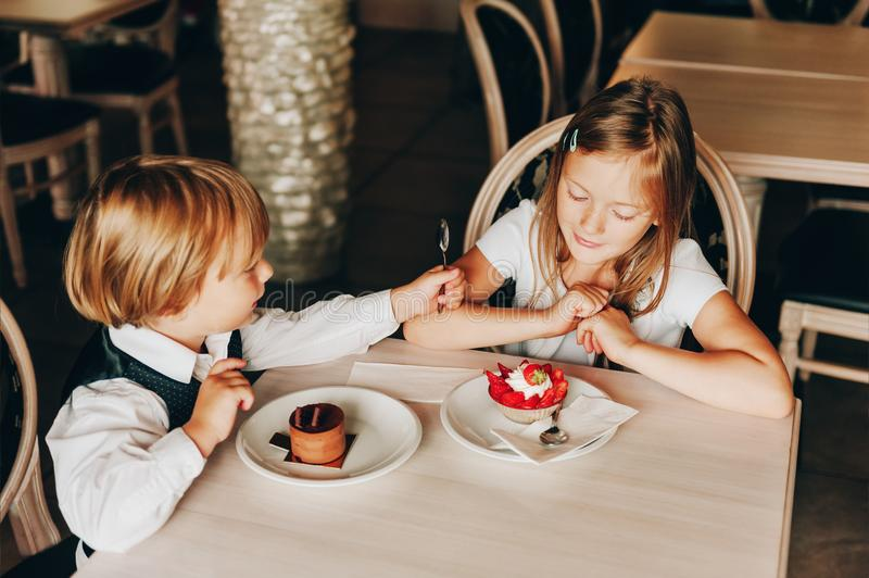 Little kids enjoying delicious desserts royalty free stock photography