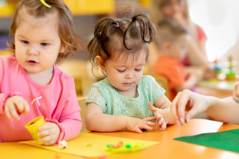 Little kids having fun together with colorful modeling clay at daycare. Children play with plasticine or dough. stock image