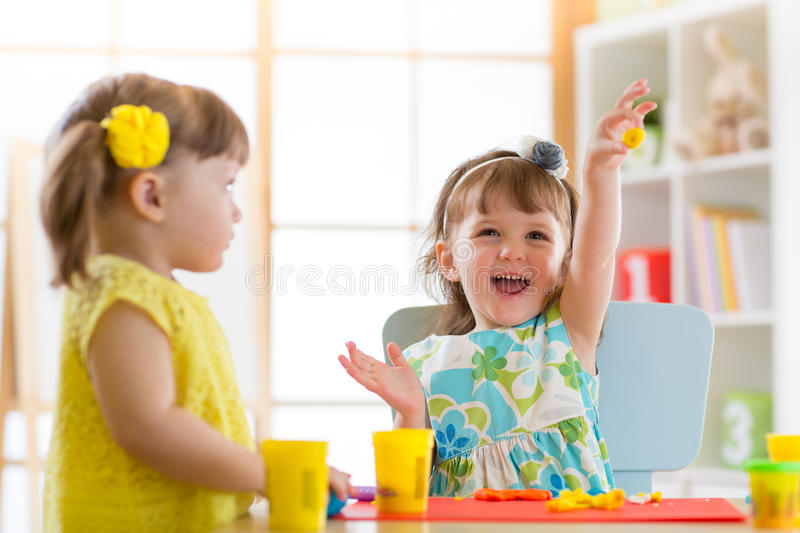 Little kids having fun together with colorful modeling clay at daycare. Creative kids molding at home. Children girls play with pl. Little kids have a fun royalty free stock images