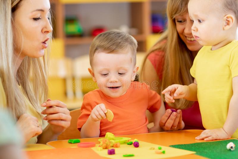 Little kids having fun together with moms. Creative kids molding at home. Children boys play with plasticine or dough. stock images