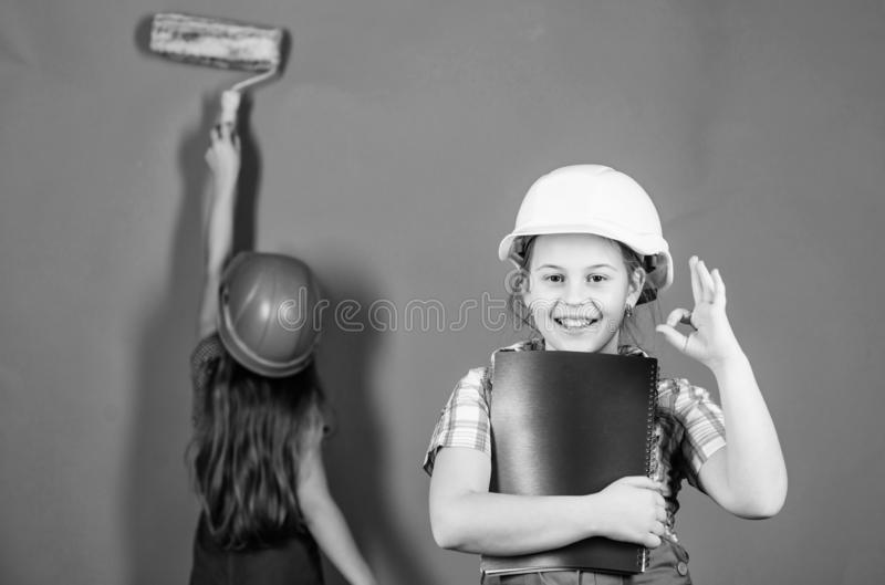 Little kids in helmet with tablet and roller. engineering idea. Future career. Painting wall. Foreman inspector. Labor stock photography
