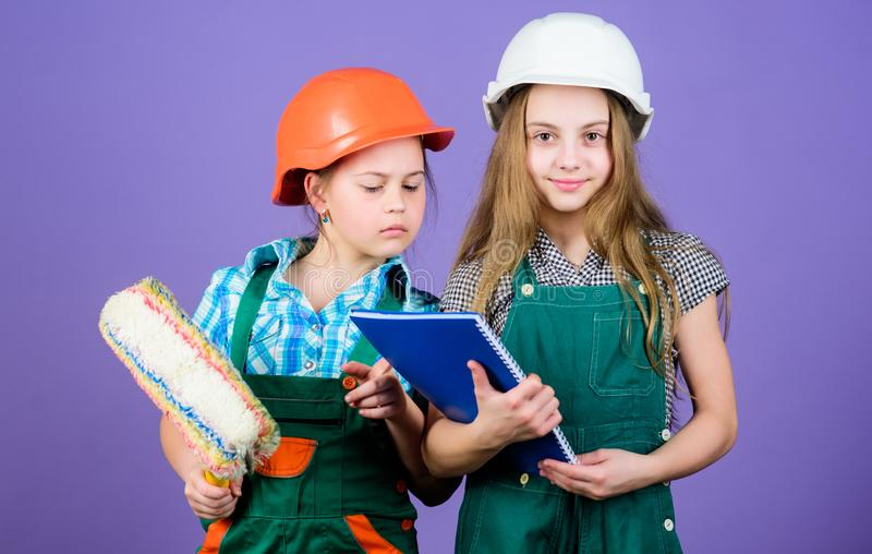Little kids in helmet with tablet and roller. small girls repairing together in workshop. school project. Labor day. 1 royalty free stock images
