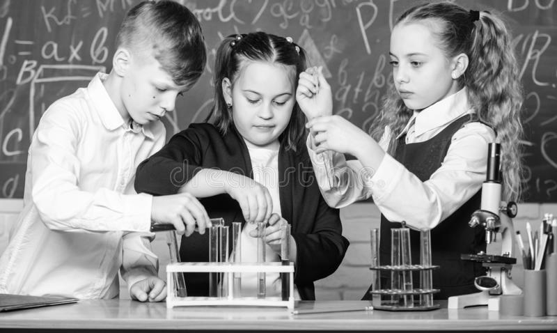 Little kids learning chemistry in school lab. students doing biology experiments with microscope. childrens day royalty free stock photos