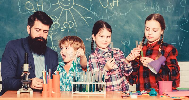 Little kids learning chemistry in school laboratory. school kids scientist studying science. happy children teacher royalty free stock photo