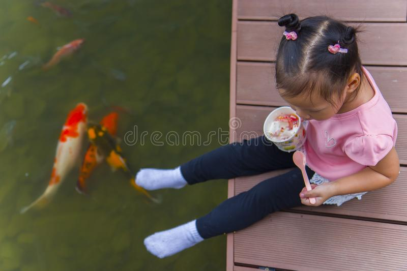 Little kids look at the water and feeding fishs on the wooden bridge. High resolution image gallery royalty free stock photos