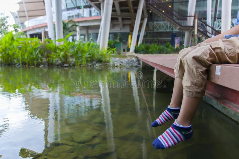 Little kids look at the water and feeding fishs on the wooden bridge. High resolution image gallery royalty free stock photo