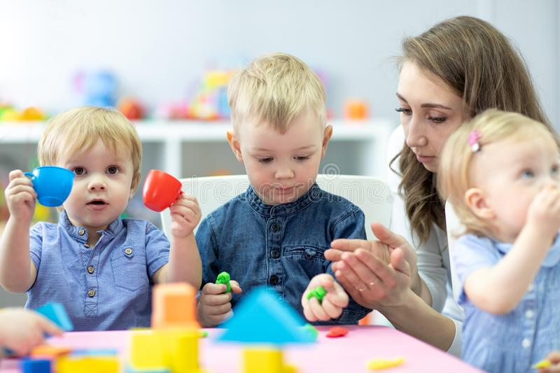 Little kids molded from clay toys. Teacher play with children. stock images