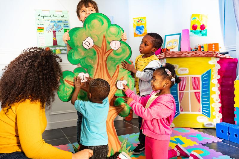 Little kids in nursery put letters on the tree stock images