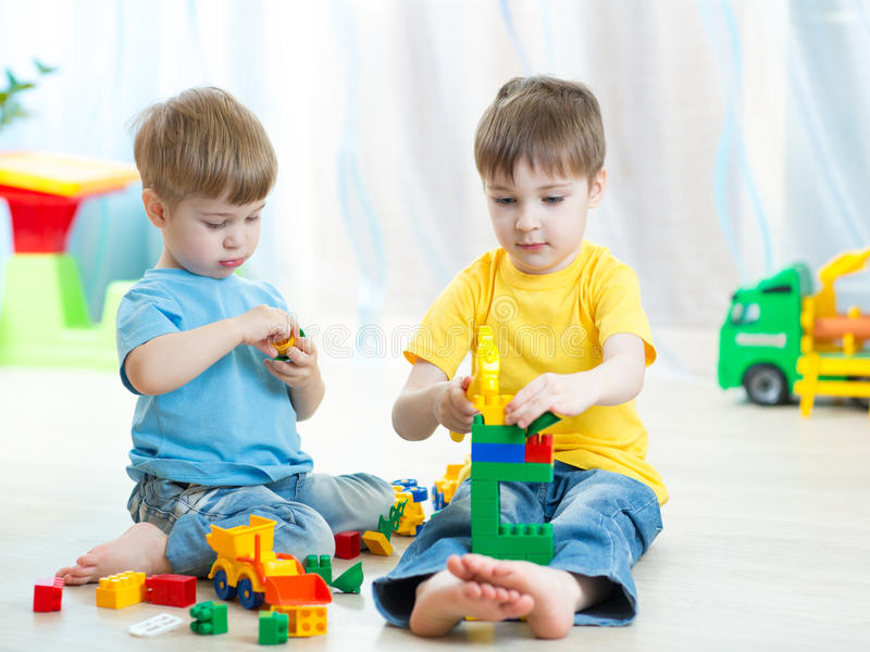 Little kids play with building bricks in preschool royalty free stock image