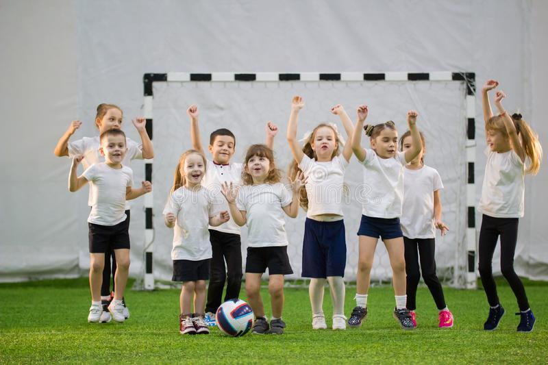 Little kids playing football indoors. Children football team. Hands up and jumping. Mid shot royalty free stock photo