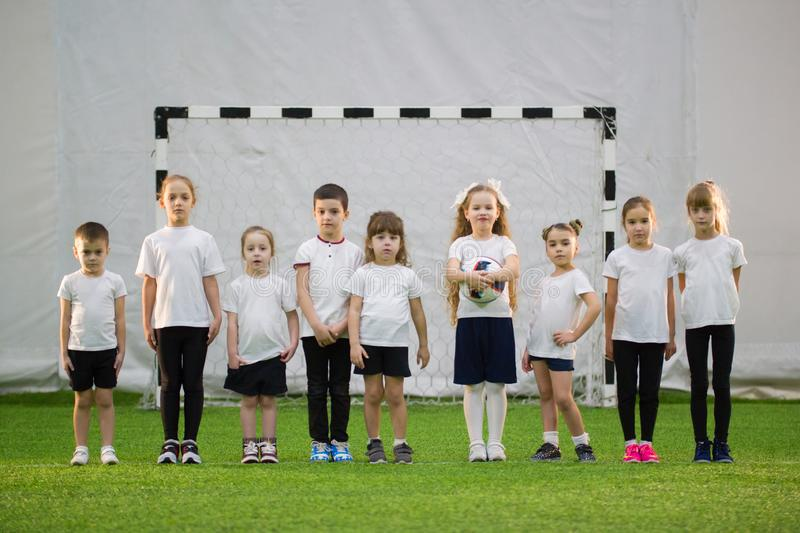 Little kids playing football indoors. Children stand in the line royalty free stock photography