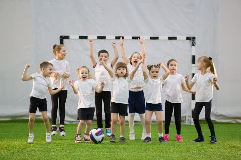 Little kids playing football indoors. Happy children football team stock photography