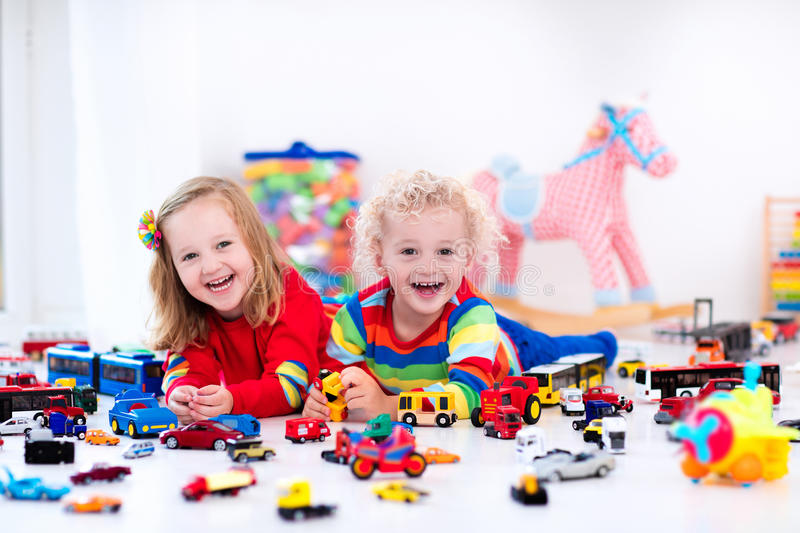 Little kids playing with toy cars. Little toddler boy and girl playing with model car collection on the floor. Transportation and rescue toys for children. Toy royalty free stock images