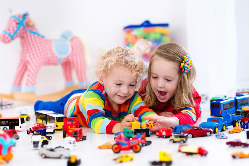 Little kids playing with toy cars. Little toddler boy and girl playing with model car collection on the floor. Transportation and rescue toys for children. Toy royalty free stock photography