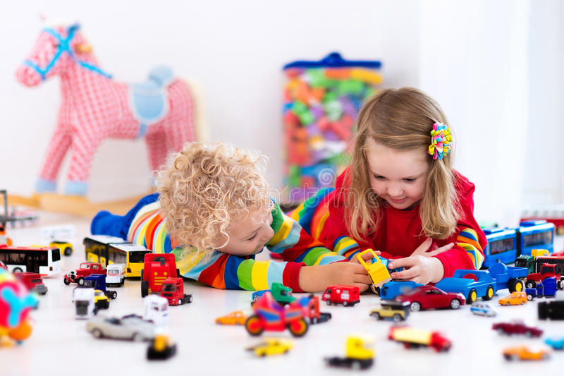 Little kids playing with toy cars. Little toddler boy and girl playing with model car collection on the floor. Transportation and rescue toys for children. Toy royalty free stock photo