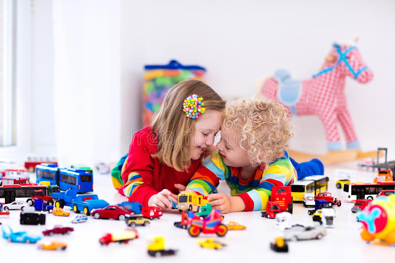 Little kids playing with toy cars. Little toddler boy and girl playing with model car collection on the floor. Transportation and rescue toys for children. Toy royalty free stock image