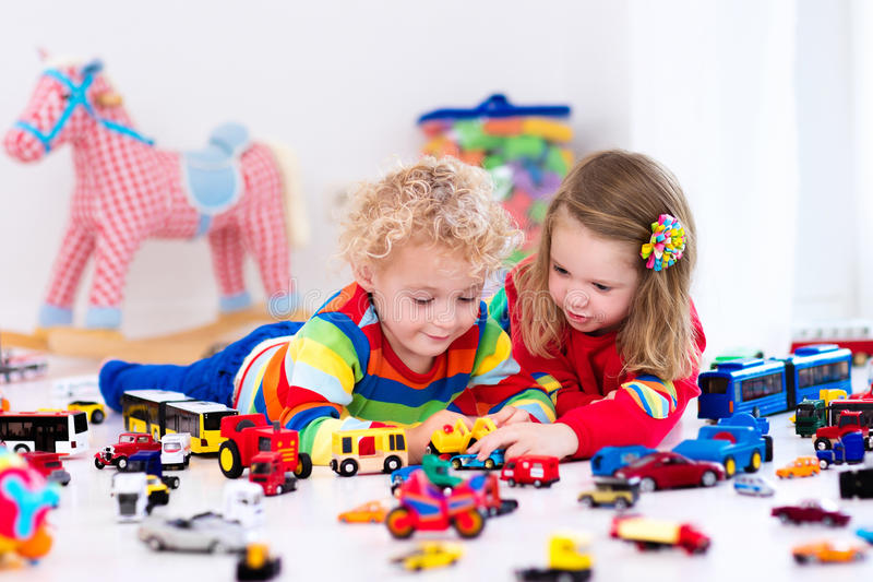 Little kids playing with toy cars. Little toddler boy and girl playing with model car collection on the floor. Transportation and rescue toys for children. Toy stock images