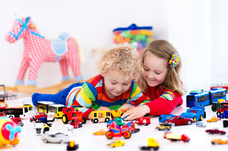Little kids playing with toy cars. Little toddler boy and girl playing with model car collection on the floor. Transportation and rescue toys for children. Toy stock photo