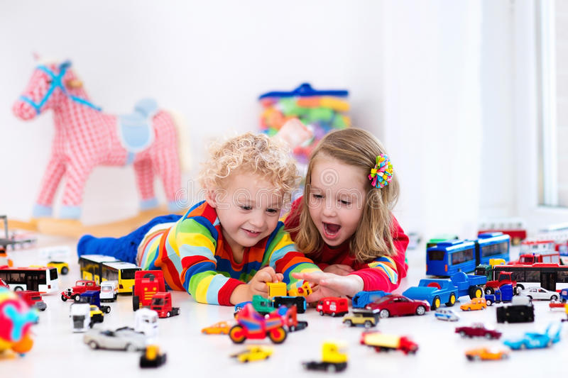 Little kids playing with toy cars. Little toddler boy and girl playing with model car collection on the floor. Transportation and rescue toys for children. Toy stock image