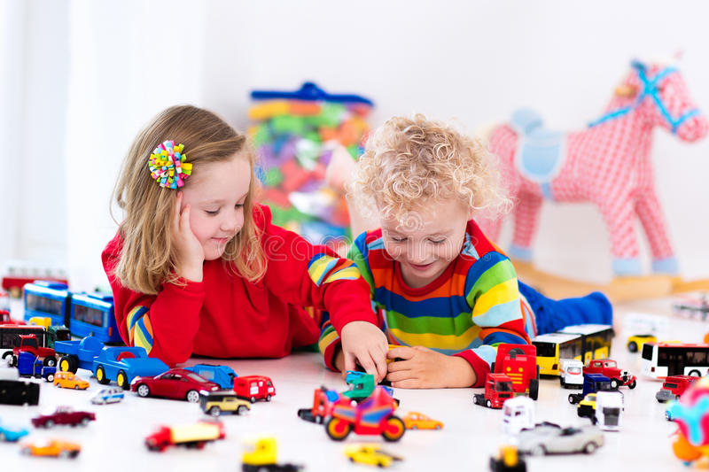 Little kids playing with toy cars. Little toddler boy and girl playing with model car collection on the floor. Transportation and rescue toys for children. Toy stock photos