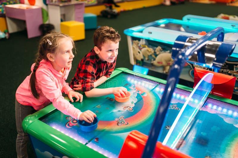 Little kids plays air hockey, entertainment center stock photography