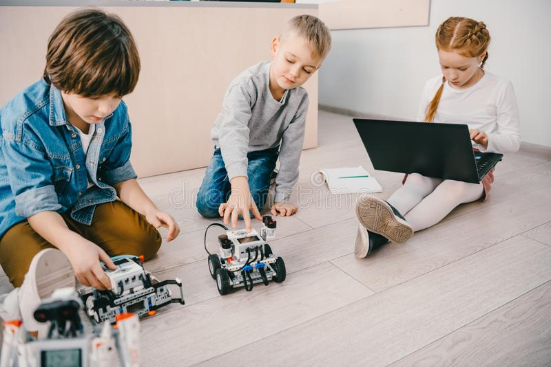 little kids sitting on floor at stem education class with robots stock photography