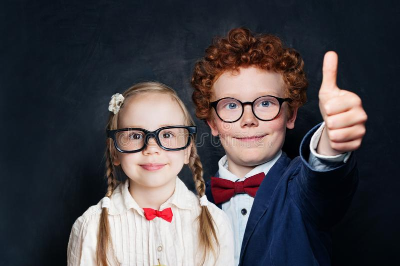 Little kids student showing thumb up, smiling and having fun against chalkboard background stock photos