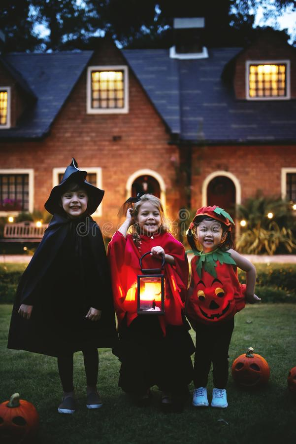 Little kids trick or treating in Halloween stock photo