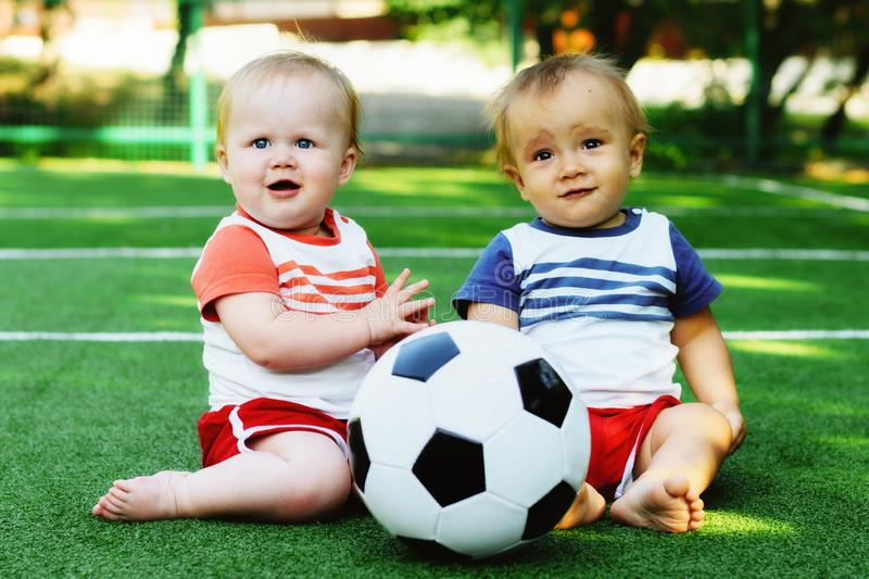 Little kids in uniform learning to play with soccer ball at sports ground. Little boy and blonde girl playing with football ball. Little kids in sports uniform royalty free stock photo