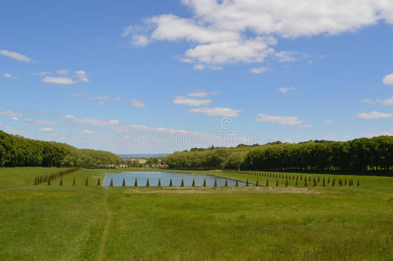 Little lake with trees around it in park. Photo of little lake with trees around it on field in The Marly Estate park in Louveciennes, bright blue sky in stock images