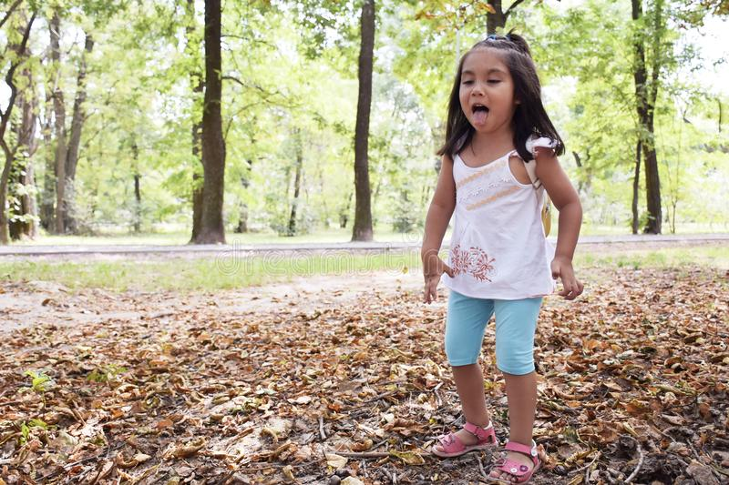 Little latin girl showing tongue in the autumn forest stock images