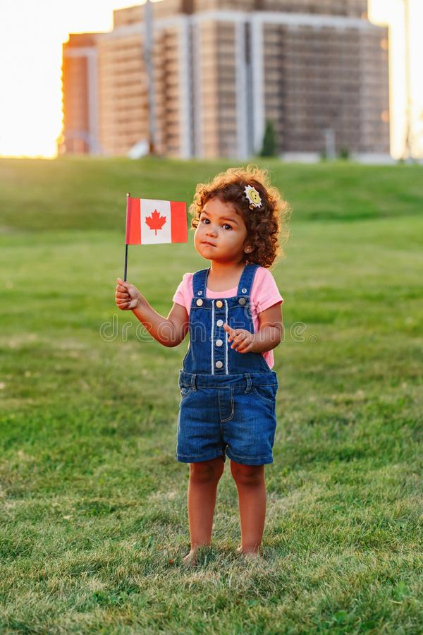 Little latin hispanic baby toddler girl holding waving Canadian flag. Portrait of adorable cute little latin hispanic baby toddler girl holding waving Canadian stock photo