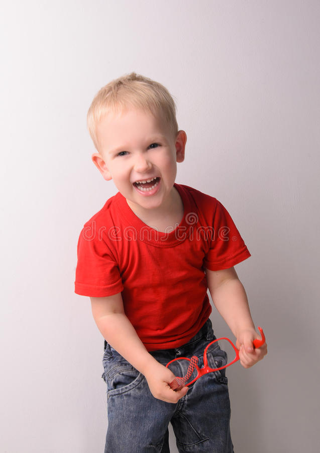 Little laughing blond boy in red shirt stock photo
