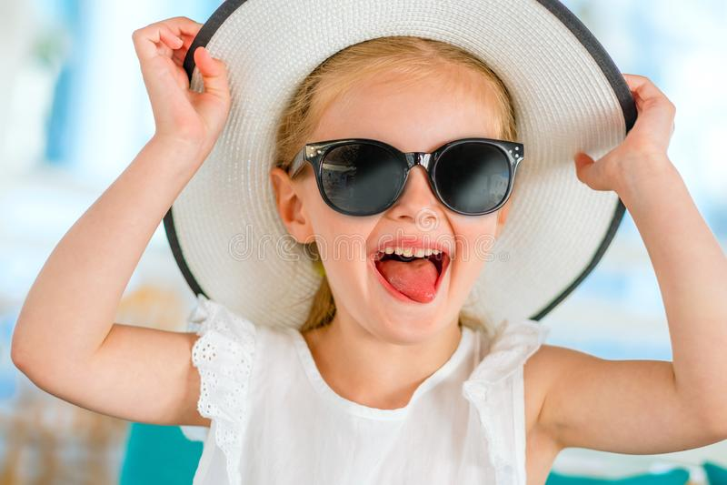 Little laughing blond girl in black sunglasses stock photography