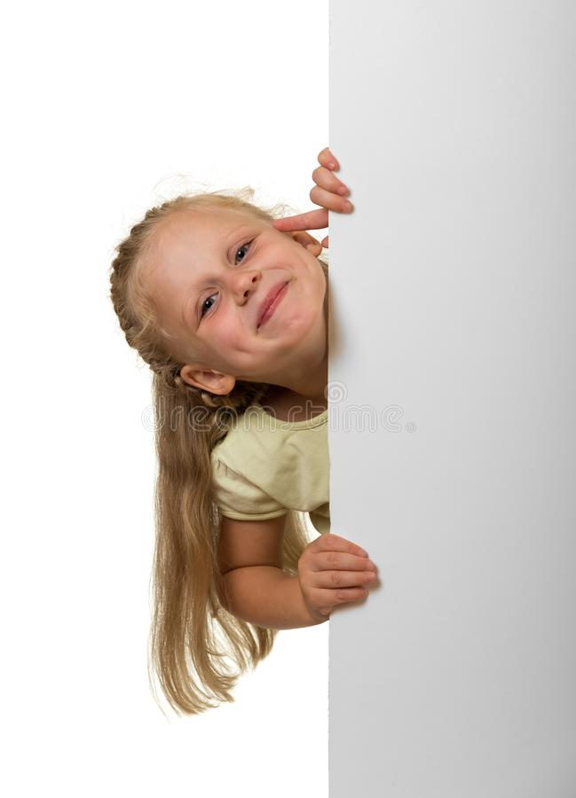 Little laughing girl peeking out from behind an empty banner, is stock photography