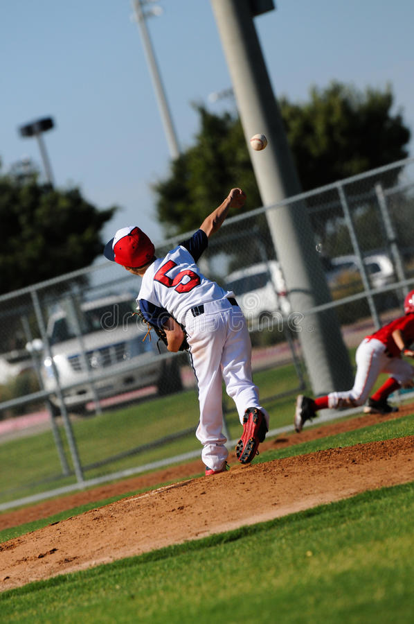 Little league pitcher throwing to first. Little league baseball pitcher throwing to first base stock photo