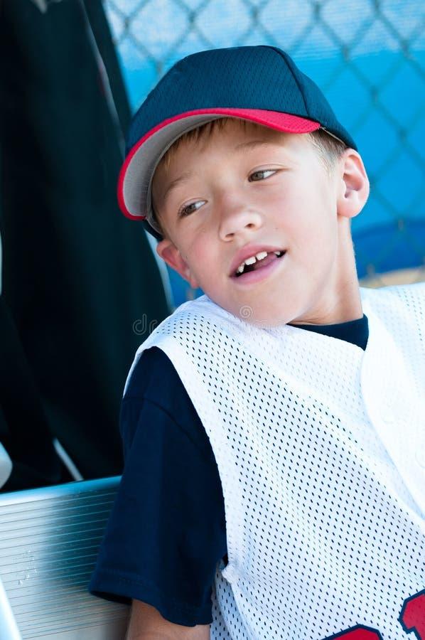 Little league baseball player in dugout. Little league baseball player smiling in dugout stock photos