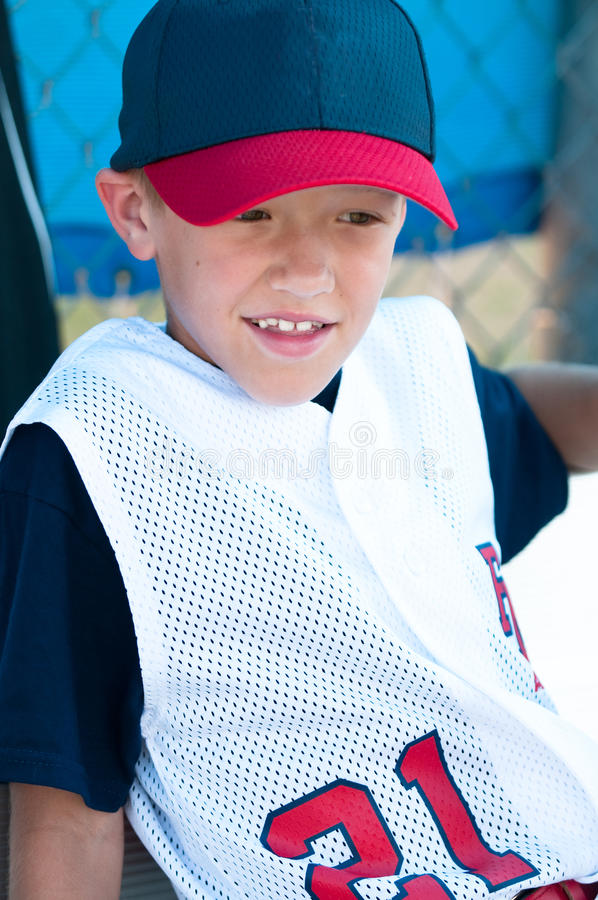 LIttle league baseball player in dugout. Little league baseball player watching from the dugout royalty free stock images