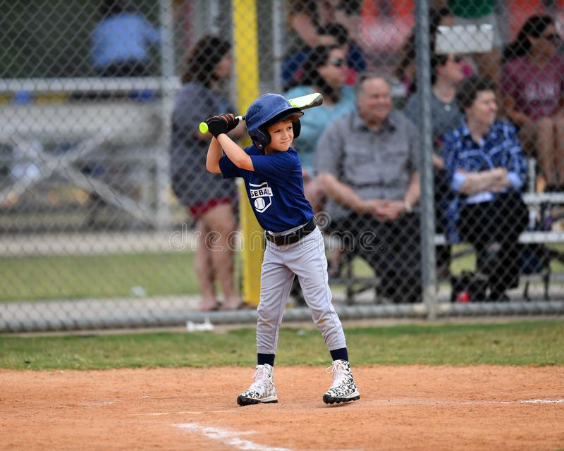 Young Boy batting during a Little League baseball game. Little league baseball player during a YMCA baseball game. Boy is at the plate swinging the bat and stock images