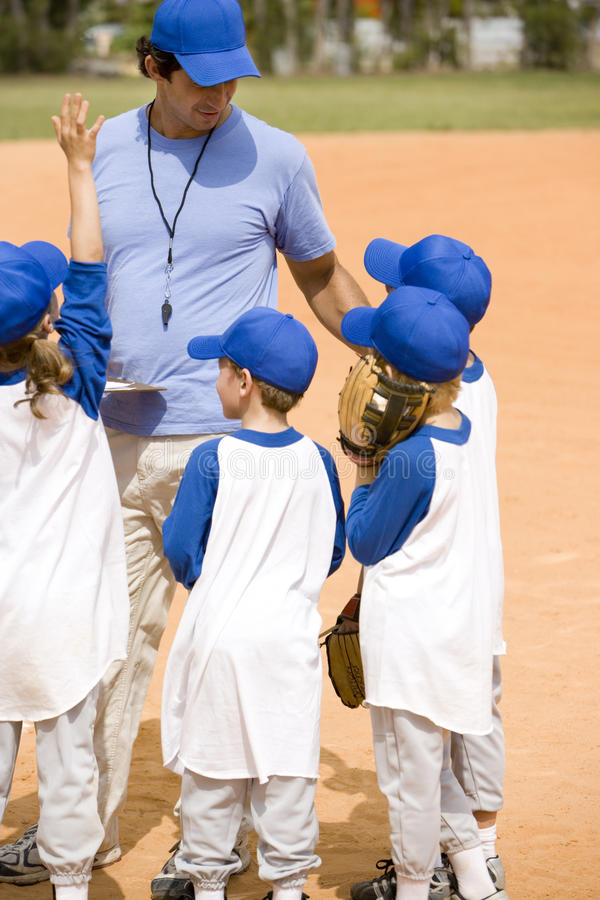 Little league baseball team and coach on pitch stock photography