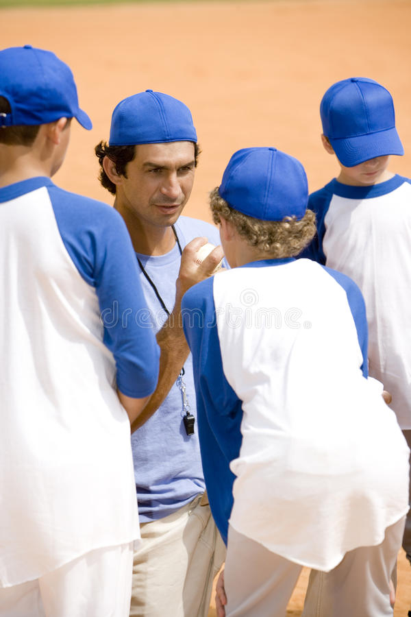 Little league baseball team and coach on pitch royalty free stock photo