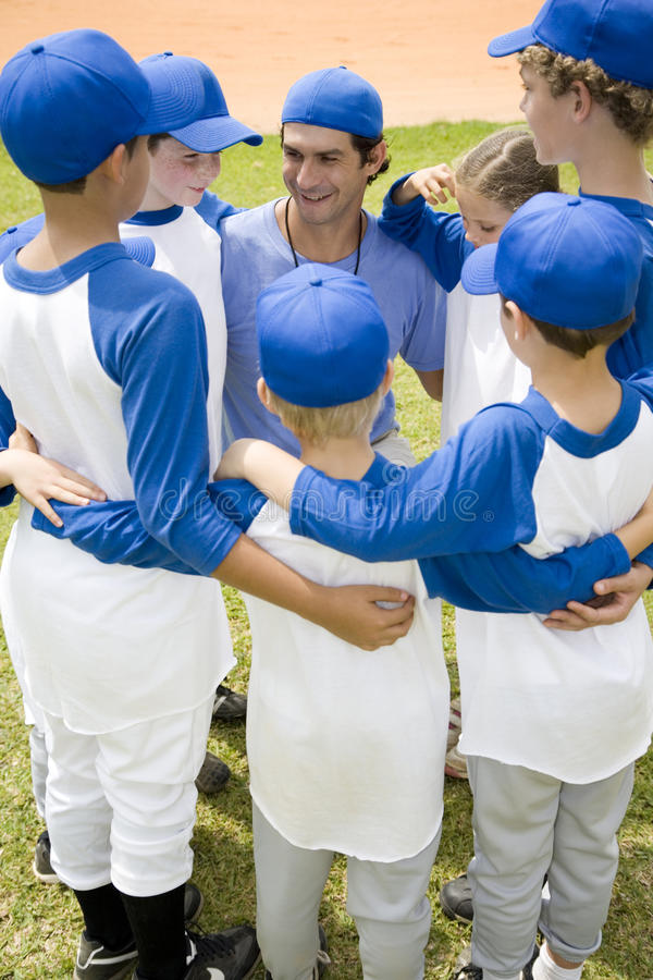Little league baseball team in huddle with their coach royalty free stock image