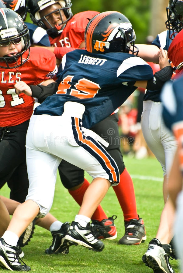 Little League Football. A lineman rushing forward to make a tackle during a little league football game. A team of 7-8-9 year old boys during a game at the royalty free stock photography