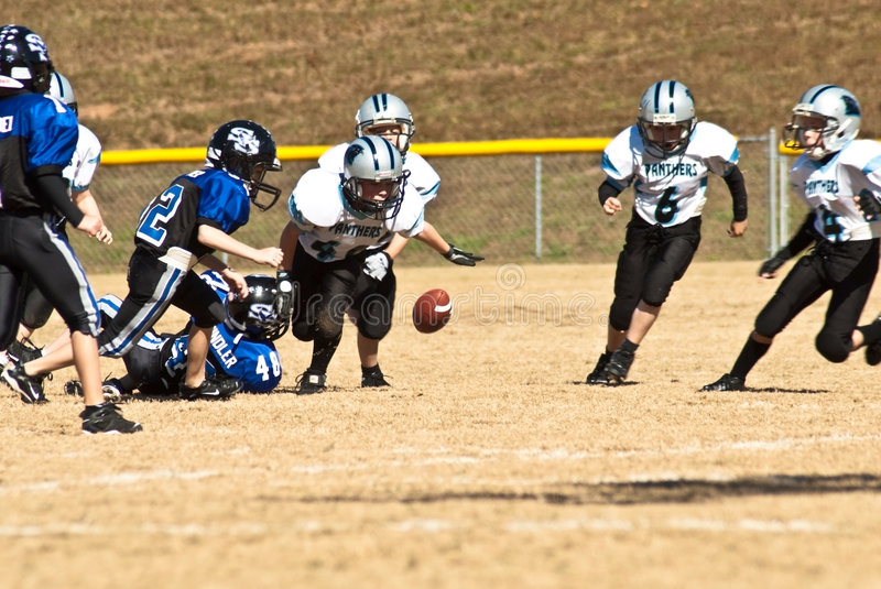 Little League Football/Loose Ball. Group of young boys on the football field chasing a loose ball. A boys team of 8-9 year olds during a game at the Forsyth royalty free stock image